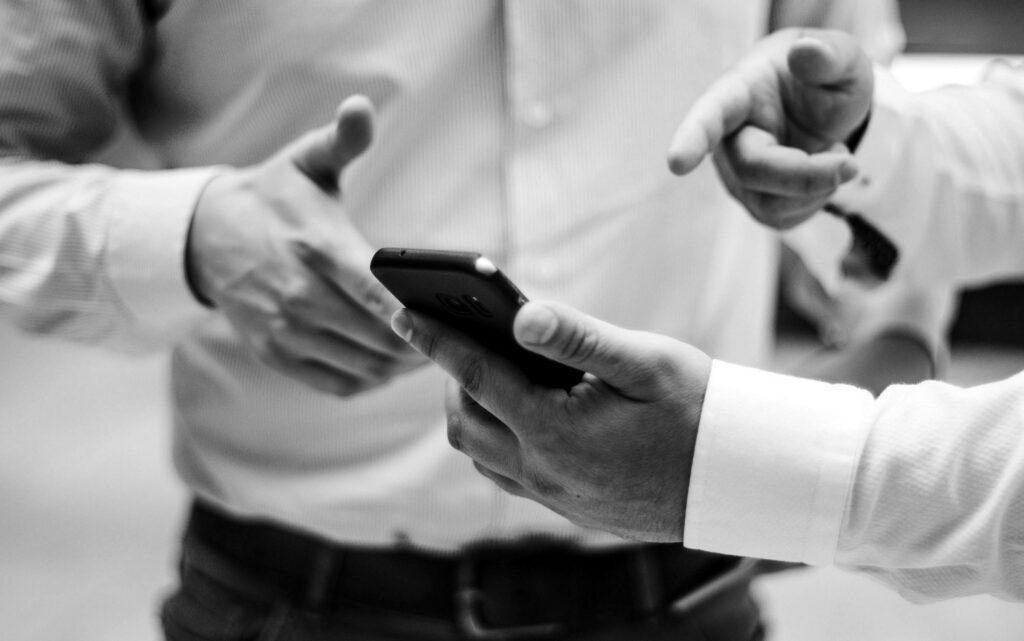 Accountant holding black smart phone. Photo by Luis Villasmil on Unsplash.